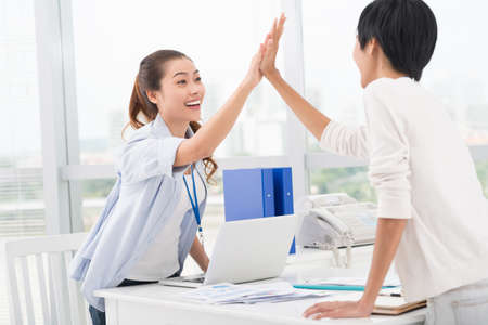 asian businesswoman: Copy-spaced image of cheerful businesswomen giving high-five in the sign of success collaboration and agreement