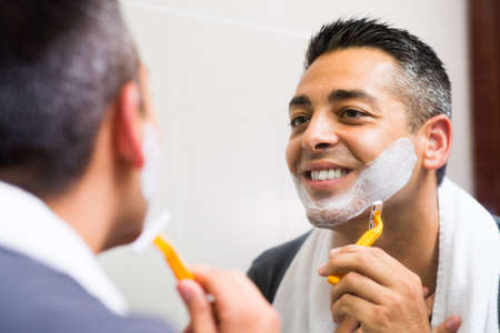 Close-up image of a shaving man looking in the mirror and smiling on the foreground Stock Photo