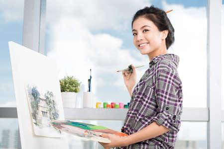 Kopieren Sie-in einem Abstand Porträt eines jungen Malers, der Kamera lächelt und betrachtet Standard-Bild