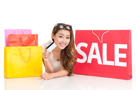 shoppingbag: Copy-spaced portrait of a cheerful shopper lying down and showing a credit card on white Stock Photo