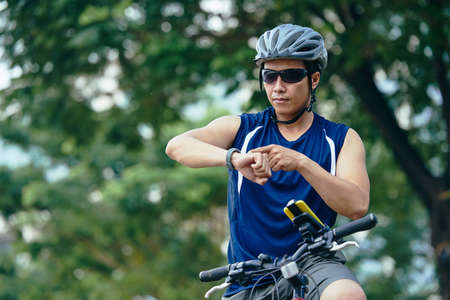 Portrait of man checking fitness tracker after cycling