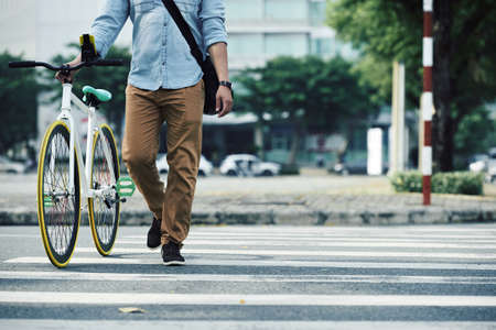 road bike: Man walking next to his bike when crossing the road