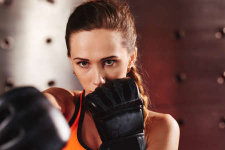competitive sport: Face of serious female boxer practicing punch