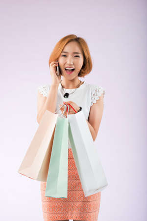 paperbags: Excited Asian girl with paper-bags calling on the phone