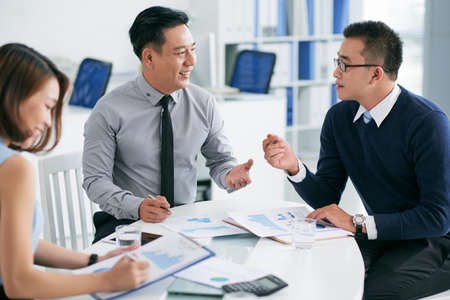 Coworkers discussing financial reports at the meeting Stock Photo
