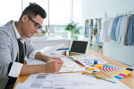 designer: Smiling Asian fashion designer creating colorful sketches for new collection