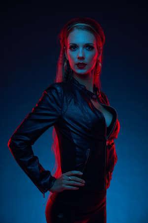 jacket: Mujer joven atractiva en la chaqueta de cuero negro sobre fondo oscuro Foto de archivo