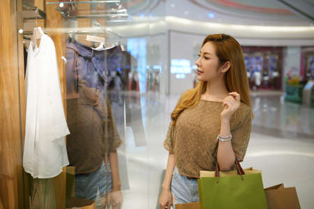 shoppingbag: Beautiful woman looking at clothes in shop windows