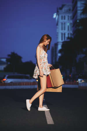 shoppingbag: Young woman with shopping bags walking outdoors at night