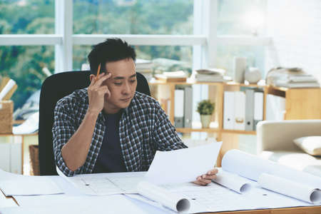 asian architect: Pensive architect working with papers in office