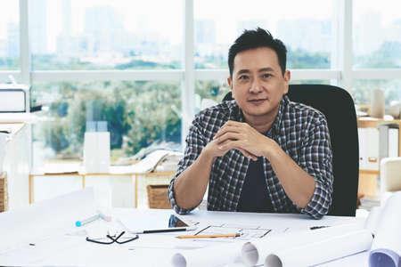 singaporean: Portrait of smiling Singaporean engineer at his workplace Stock Photo