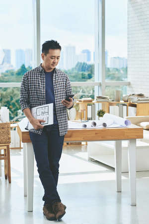 asian architect: Asian architect with blueprint and smartphone text messaging Stock Photo