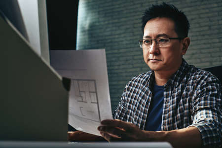 singaporean: Concentrated Singaporean architect looking at blueprint of apartment