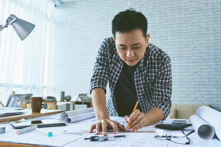 Singaporean architect concentrated on work on blueprint