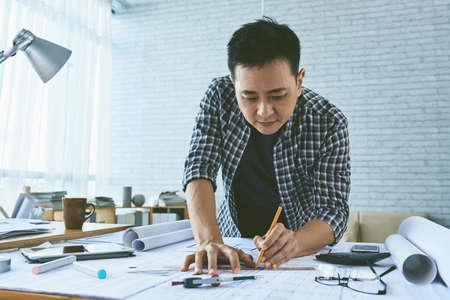 singaporean: Singaporean architect concentrated on work on blueprint