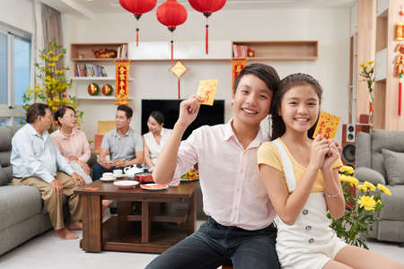 Asian brother and sister showing lucky money envelopes they got for Tet celebration