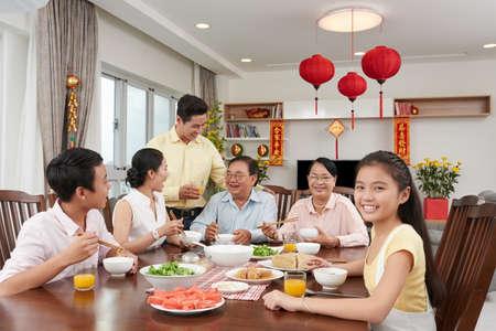 Happy Vietnamese little girl enjoying New Year dinner with family