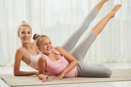 girl lying: Happy girl and her mother performing exercise when lying on the floor