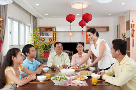 Woman bringing main dish to dinner table for Tet celebration
