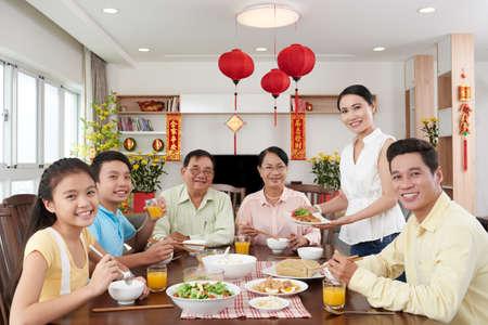 Gelukkige Vietnamese familie die diner voor Tet-viering hebben