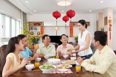 Smiling woman serving family dinner for Tet celebration Stock Photo