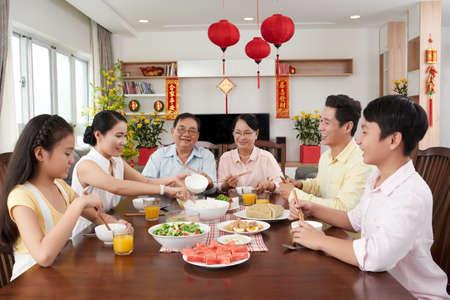 Aziatische familie die bij grote lijst voor Nieuwjaarviering eet