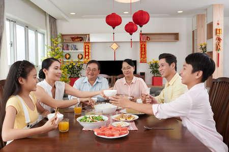 Vietnamese familie die en bij Tet-viering babbelen eten Stockfoto