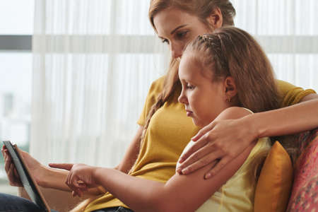 Mother hugging her daughter when they are watching tv shows Stock Photo