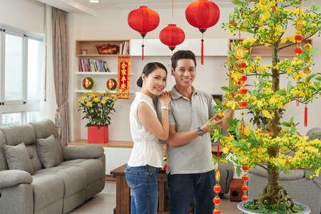 Man en vrouw versieren huis voor Tet viering