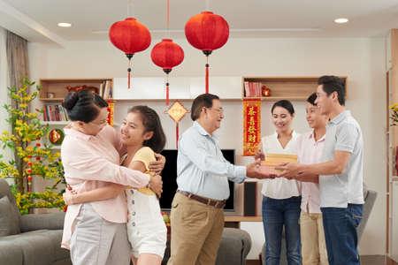 Familia asiática intercambia regalos en la celebración de Tet