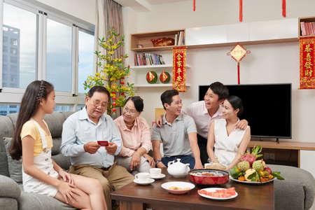 Vietnamese family drinking tea and having fun at Tet celebration Stock Photo