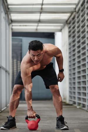 Sportsman looking at camera when lifting kettlebell