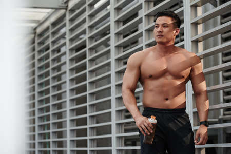 Muscular Asian guy smiling and looking at side