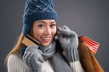 Close-up portrait of a lovely woman in warm knitted wearing doing the winter shopping