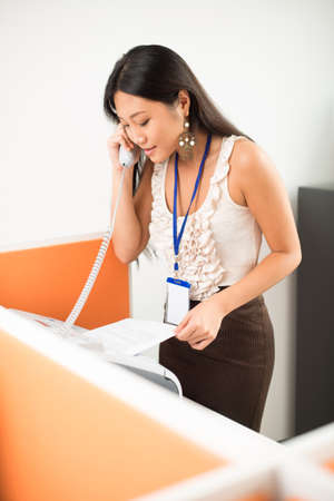 Office worker answering the call and printing documents Stock Photo