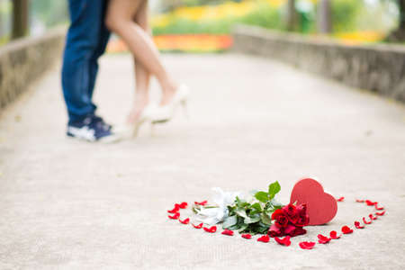 Heart shape with gift box and flowers inside with couple in the background