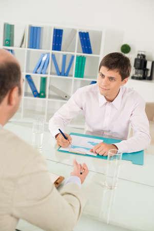 Image verticale d'un employé discutant de la stratégie de l'entreprise avec son patron au premier plan Banque d'images - 70348623