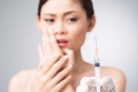 Woman looking at a syringe in fear Stock Photo