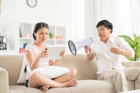 Image d'une fille adolescente en réseau avec une tablette numérique tandis que son père lui criait dessus avec le mégaphone au premier plan Banque d'images - 70348675