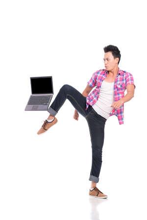 kicking: Teenage boy kicking his laptop