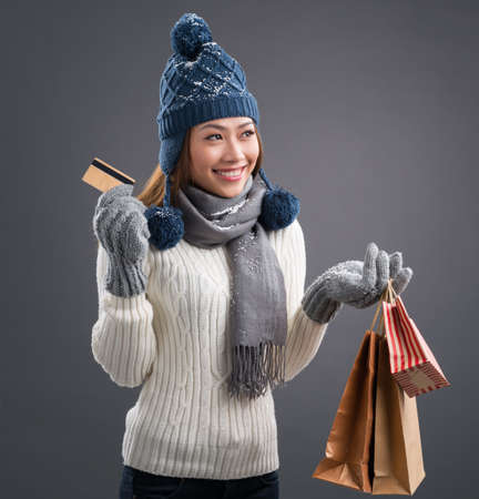 Image of a young winter lady in warm wearing with shopping bags and a credit card in hands over grey