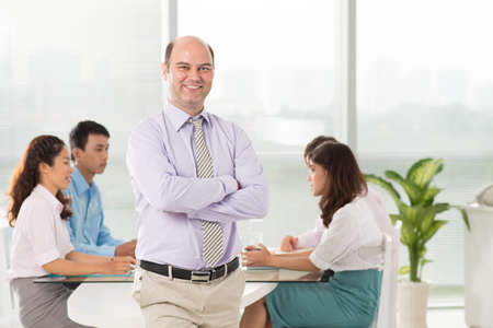 Portrait of a professional manager smiling and looking at camera on the foreground