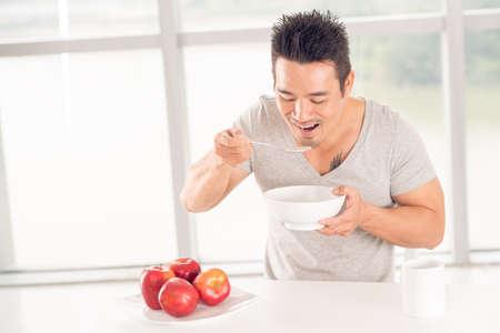 Happy guy breakfasting with porridge and apples Stock Photo