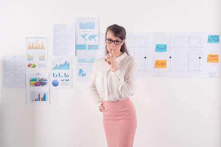 guardar silencio: Copia a espacio retrato de una empresaria joven que presenta a la cámara mientras está de pie delante de la pared con los gráficos y diagramas de negocios