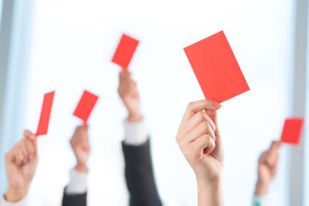 objection: Cropped image of human hands declining something showing red card on the foreground