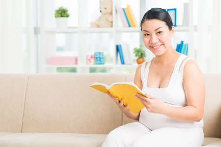Copy-spaced portrait of a happy pregnant woman reading a book at home on the foreground