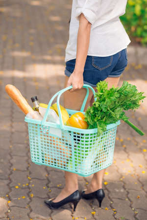 Cropped vertical image of a woman with a shopping basket full of food products