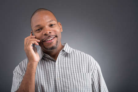 cutouts: Close-up portrait of a black man calling by phone and looking at camera