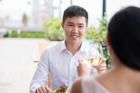Copy-spaced image of a young man having lunch at a restaurant with his girlfriend on the foreground Stock Photo