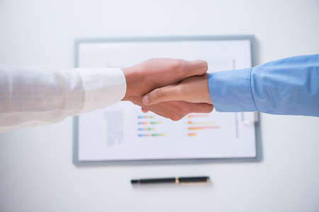 ovation: Below view of human handshaking in the sign of agreement on the foreground